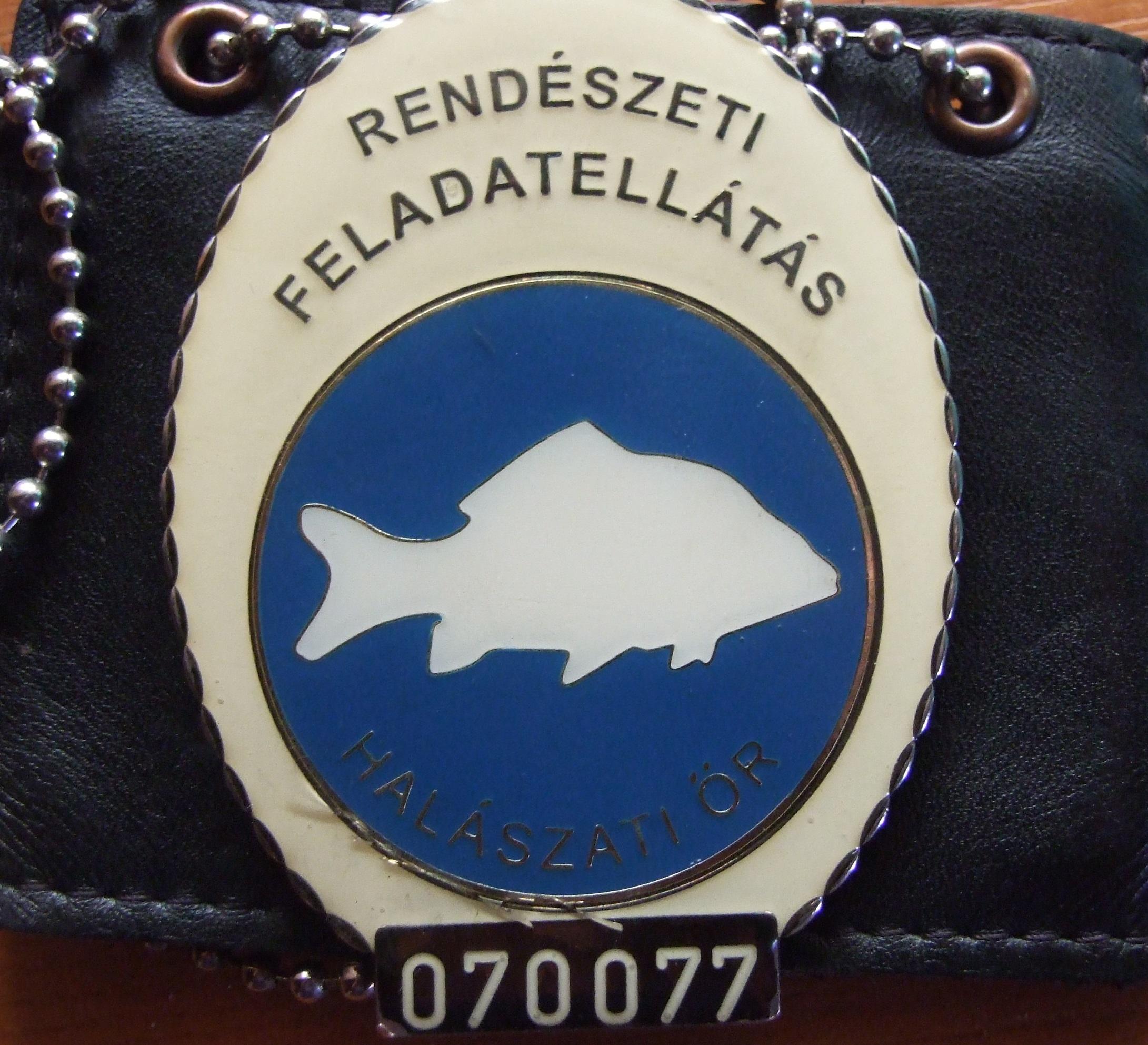 Hivatásos halőrök jelvénye. Az állami halőröké hasonló csak azon  egy harcsa sziluettje található és rajta van a címer is.