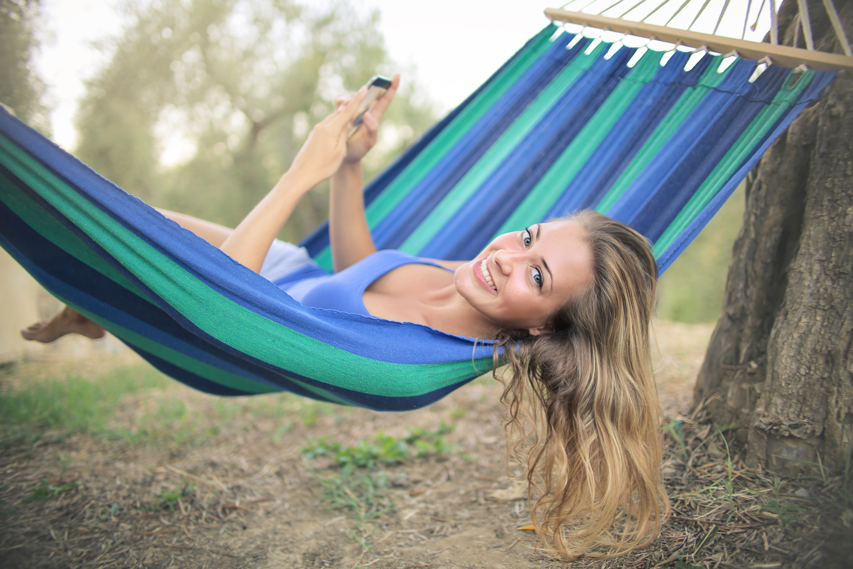 cheerful-young-woman-resting-in-colorful-hammock-3771818.jpg