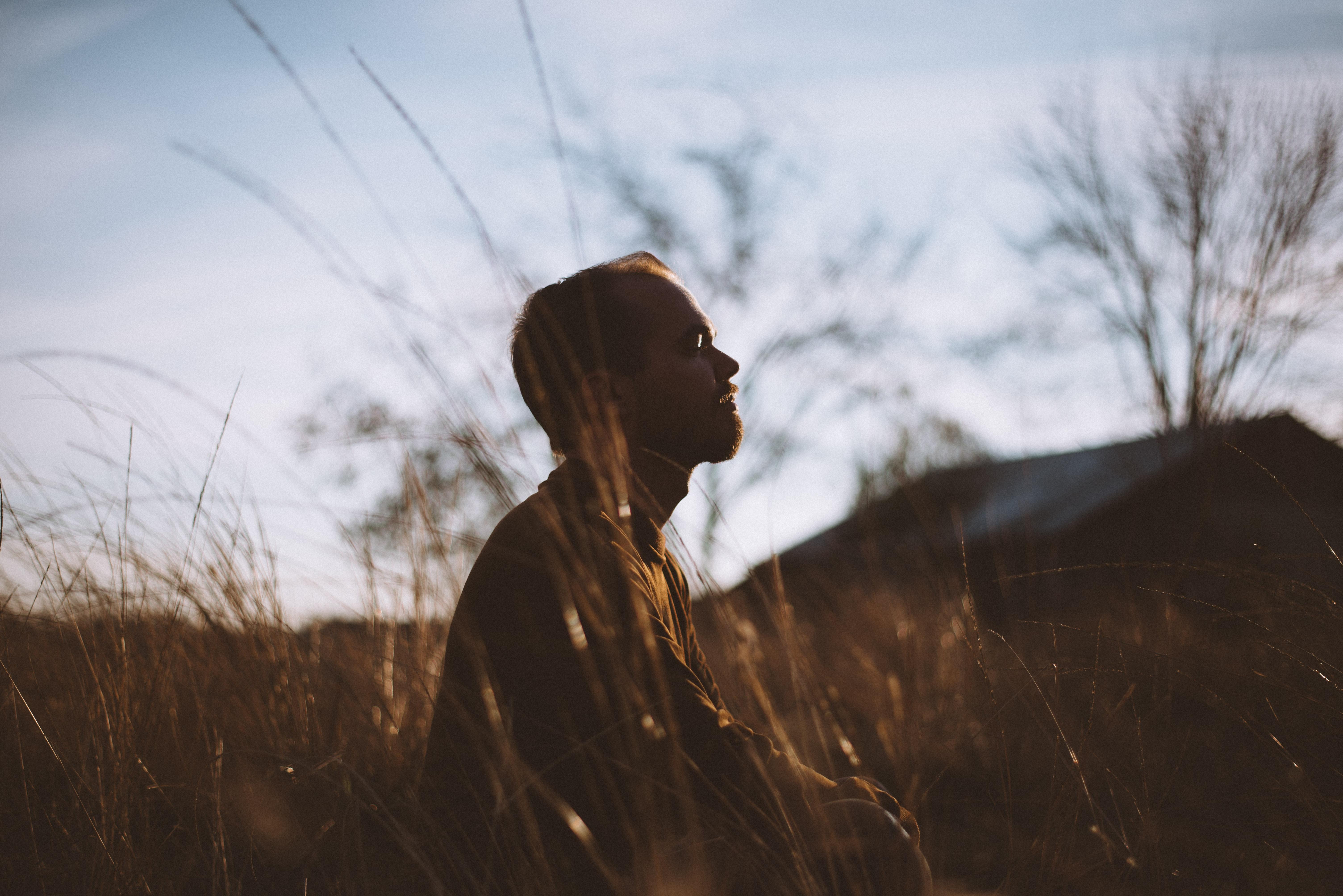 silhouette-of-man-sitting-on-grass-field-at-daytime-775417.jpg