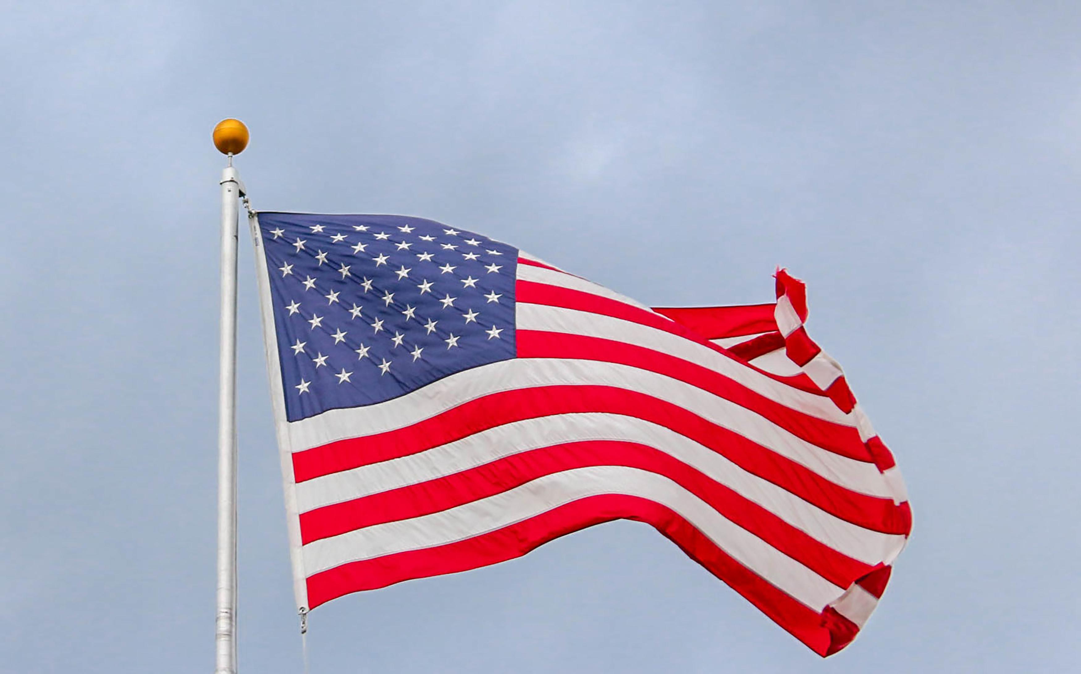 usa-flag-waving-on-white-metal-pole-1550342.jpg