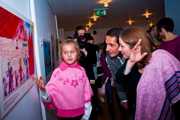 Maczó Vanessza  a bicskei Kossuth Zsuzsa Gyermekotthon lakója Tamara Guttman kanadai nagykövetnek és Papp Tamás  politikai- és sajtóreferensnek mutatja festményét. (Fotók: Hajdrák Tímea, Vizuális Világ Alapítvány)