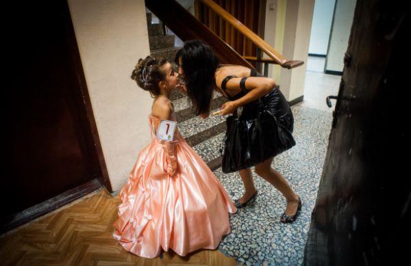 Édesanya szájon csókolja színpadra készülő gyermekét a Little Queen of the World nemzetközi gyerekszépségverseny döntjében (2010. Bulgária, Burgasz - Forrás: sajto-foto.hu)