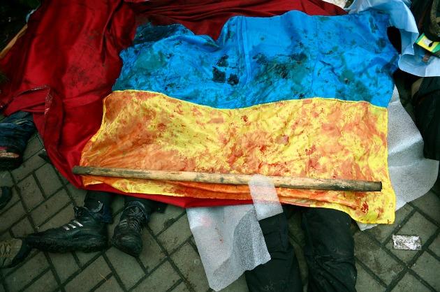 Kormányellenes tüntetők véres ukrán nemzetiszínű zászlóval letakart holtteste a kijevi Függetlenség terén, a Majdanon 2014. február 20-án. Fotó: Beliczay László (MTI/MTVA)
