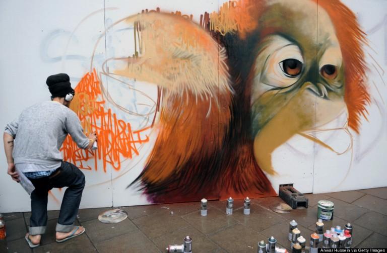 A graffitiművész épp az utolsó ecsetvonásokat végzi See No Evil című képén, mely egy street art projekt részeként készült a Nelson Streeten, 2011-ben