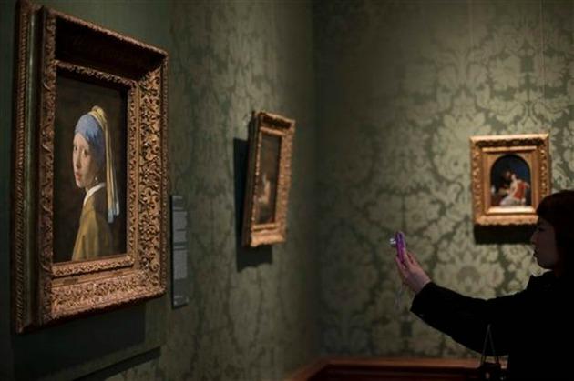 Látogató a Mauritshuisban, a Leány gyöngy fülbevalóval festmény előtt (Fotó: kansascity.com)