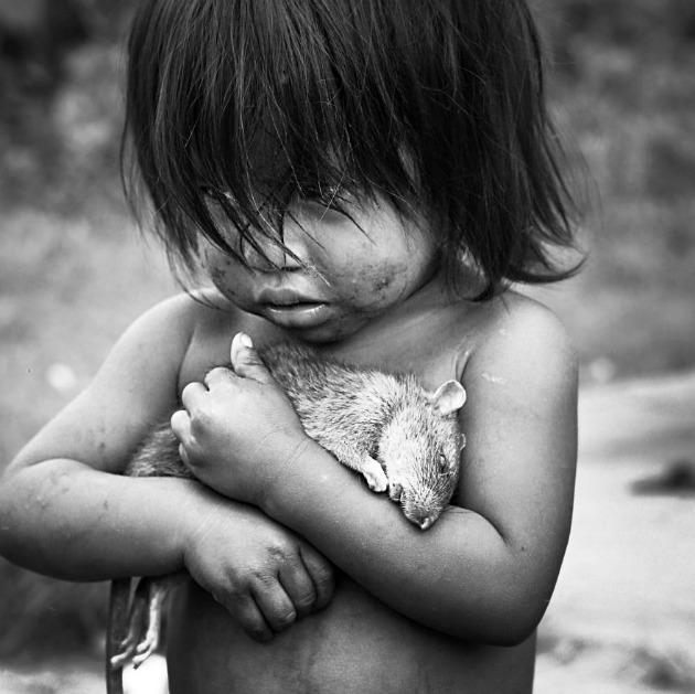 Guaraní kislány szorít magához egy döglött patkányt