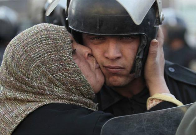 Egyiptomi nő csókol arcon egy rendőrt, aki megtagadta a parancsot, hogy a tüntetők közé lőjön