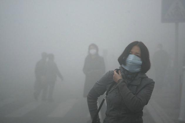 Védőmaszkos lány sétál Peking utcáin, ahol a levegőben található szennyező mikrorészecskék száma 40-szerese a nemzetközi egészségügyi határértéknek