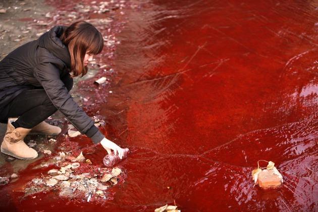 Egy újságíró mintát vesz a vörös szennyezett vízből