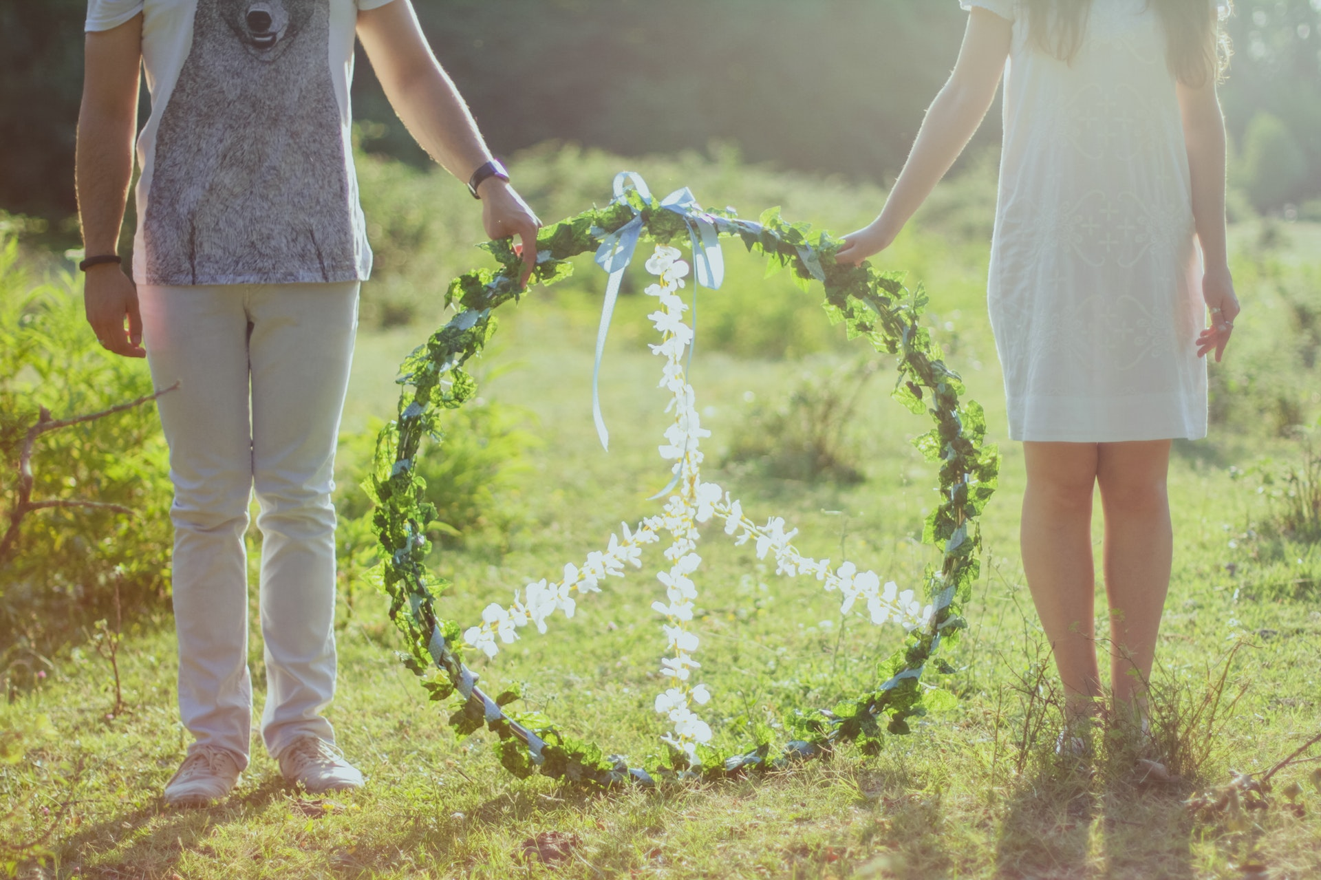 two-person-holding-white-and-green-peace-wreath-886616.jpg