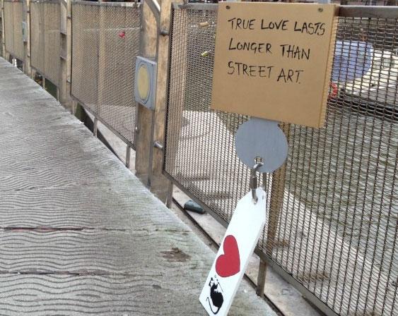 """Banksy-motívumos kulcstartó és papírlakat egy bristoli hídon. """"Az igaz szerelem tovább tart mint a street art"""""""
