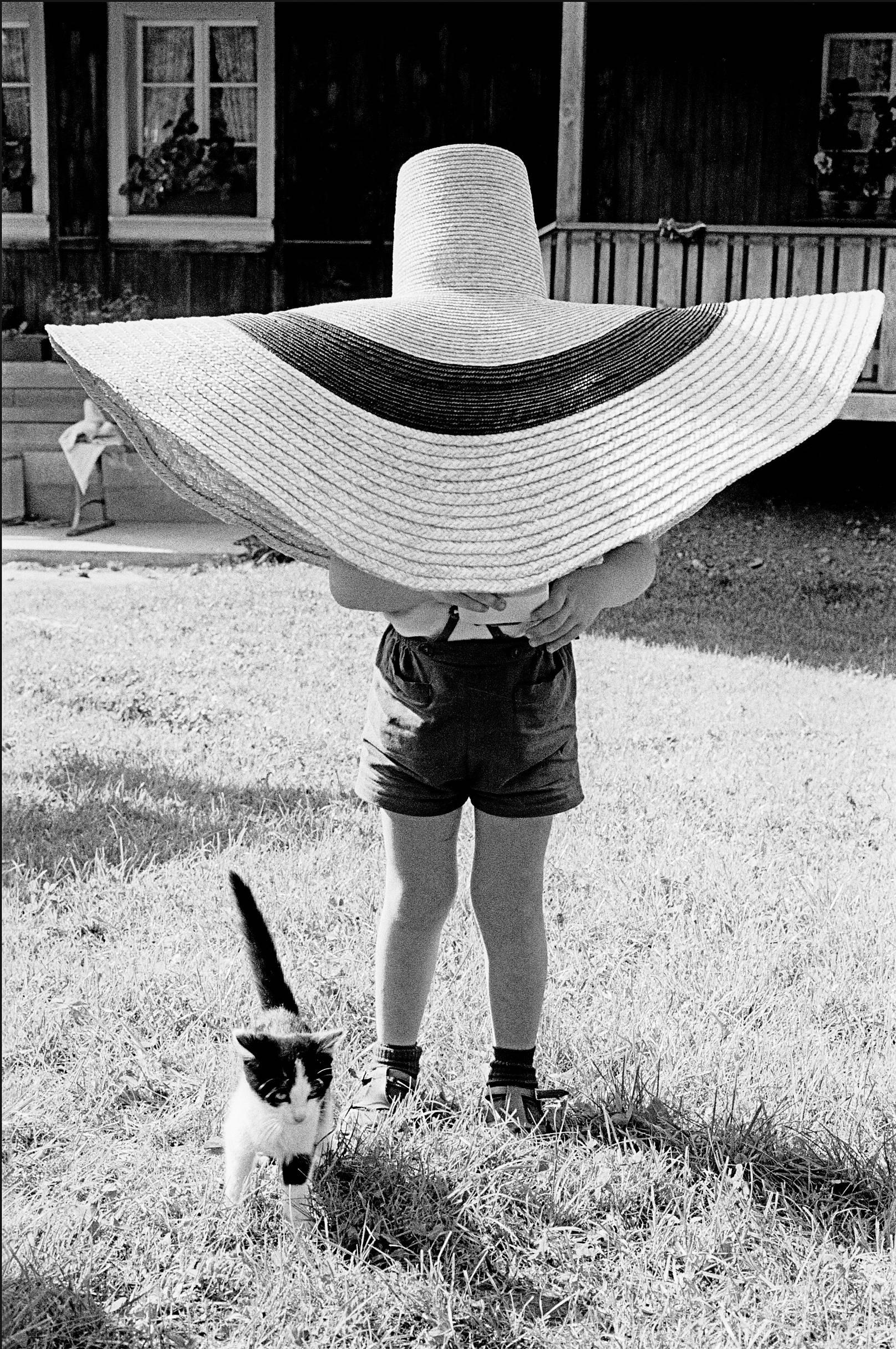 Fotó: Frank Horvat: 1959, Morgarten, Switzerland, Lorenzo under hat, with cat © Frank Horvat