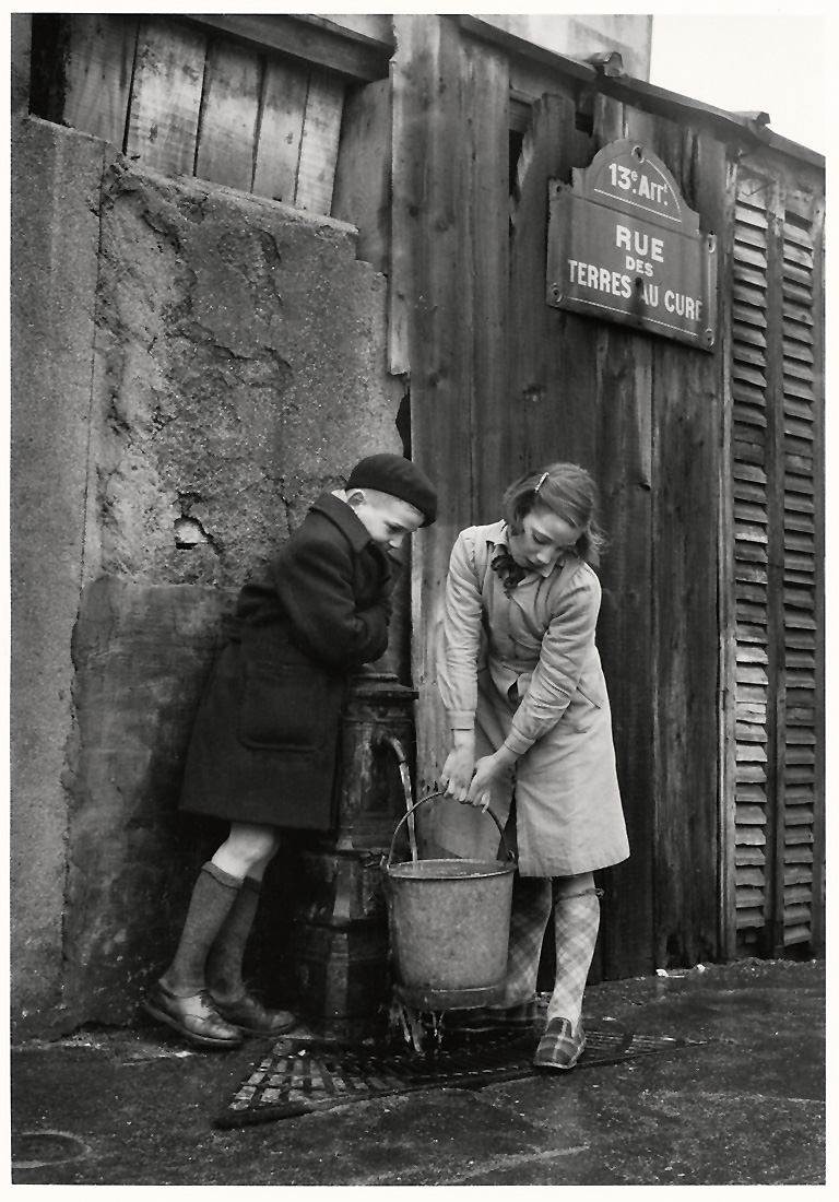 Fotó: Sabine Weiss<br />Enfants prenant de l'eau à la fontaine, rue des Terres-au-Curé<br />[Children taking water from the fountain, rue des Terres au Curé]<br />Paris, 1954<br />Silver gelatin print<br />© Sabine Weiss