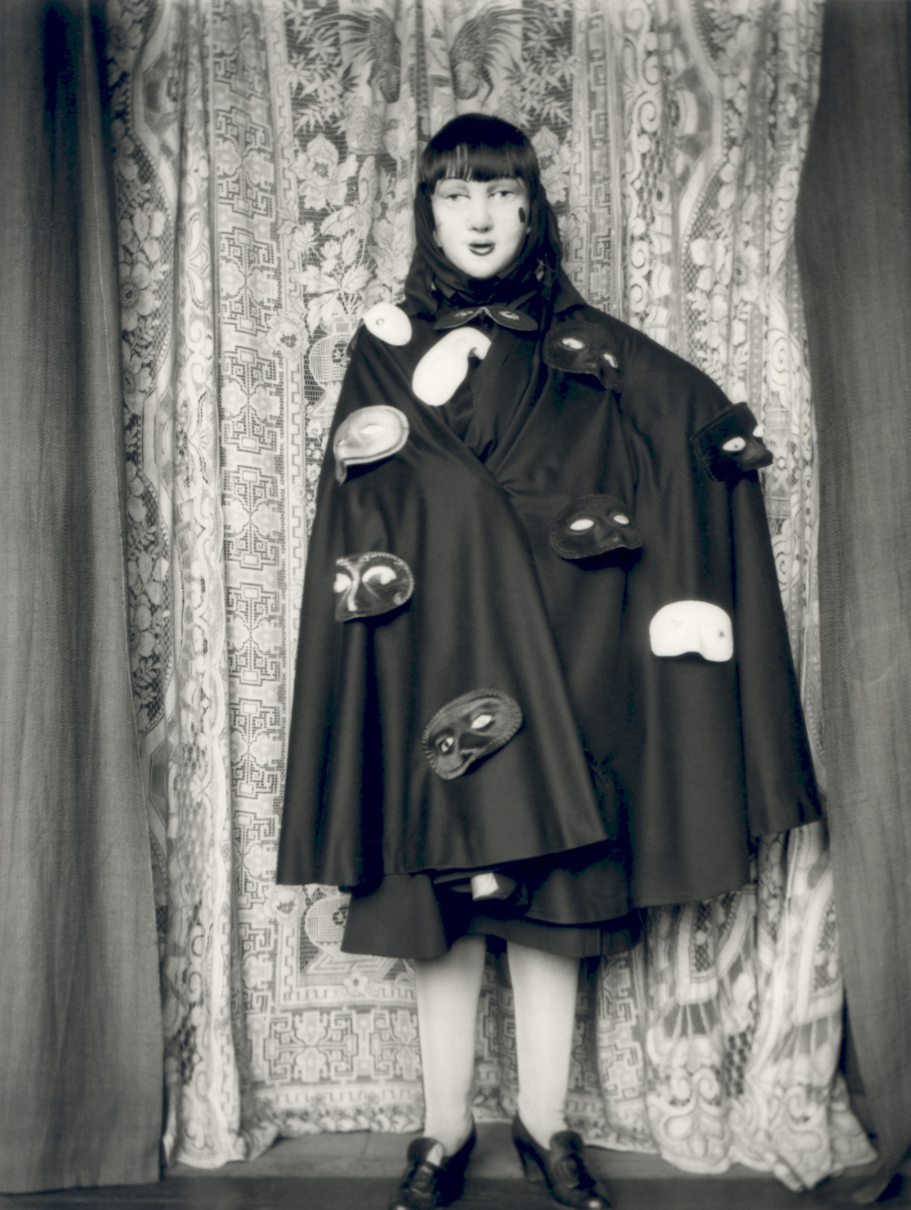 Fotó: Claude Cahun: Self-portrait (full length masked figure in cloak with masks), 1928 © Jersey Heritage Collections