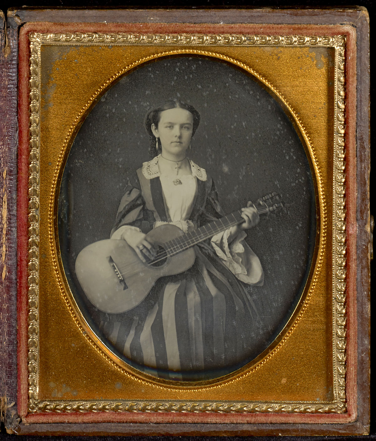Fotó: Unknown maker (American)<br />Portrait of Young Girl with a Guitar<br />c. 1850<br />Daguerreotype<br />1/6 plate<br />Open: 9.2 x 15.2 cm (3 5/8 x 6 in.)<br />Graham Nash Collection