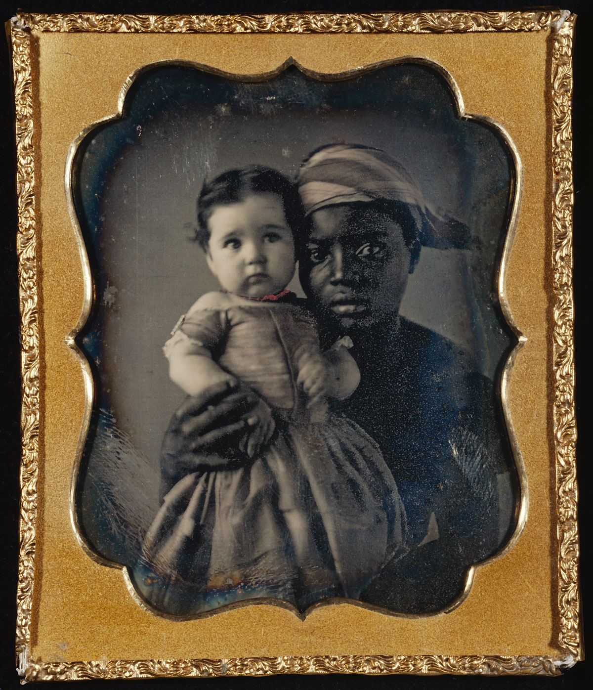 Fotó: Unknown maker (American)<br />Portrait of a Nurse and a Child<br />c. 1850<br />Daguerreotype, hand-colored<br />1/6 plate<br />Image: 6.2 x 4.8 cm (2 7/16 x 1 7/8 in.)<br />Mat: 8.3 x 7.1 cm (3 1/4 x 2 13/16 in.)<br />The J. Paul Getty Museum, Los Angeles