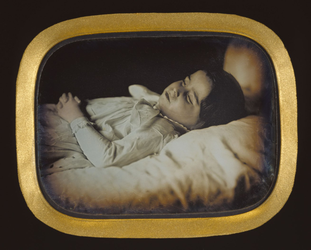 Fotó: Carl Durheim (Swiss, 1810-1890)<br />Postmortem of a Child<br />c. 1852<br />Daguerreotype, hand-colored<br />1/4 plate<br />Image: 6.8 x 9.4 cm (2 11/16 x 3 11/16 in.)<br />Object (whole): 12.7 x 15.1 cm (5 x 5 15/16 in.)<br />The J. Paul Getty Museum, Los Angeles