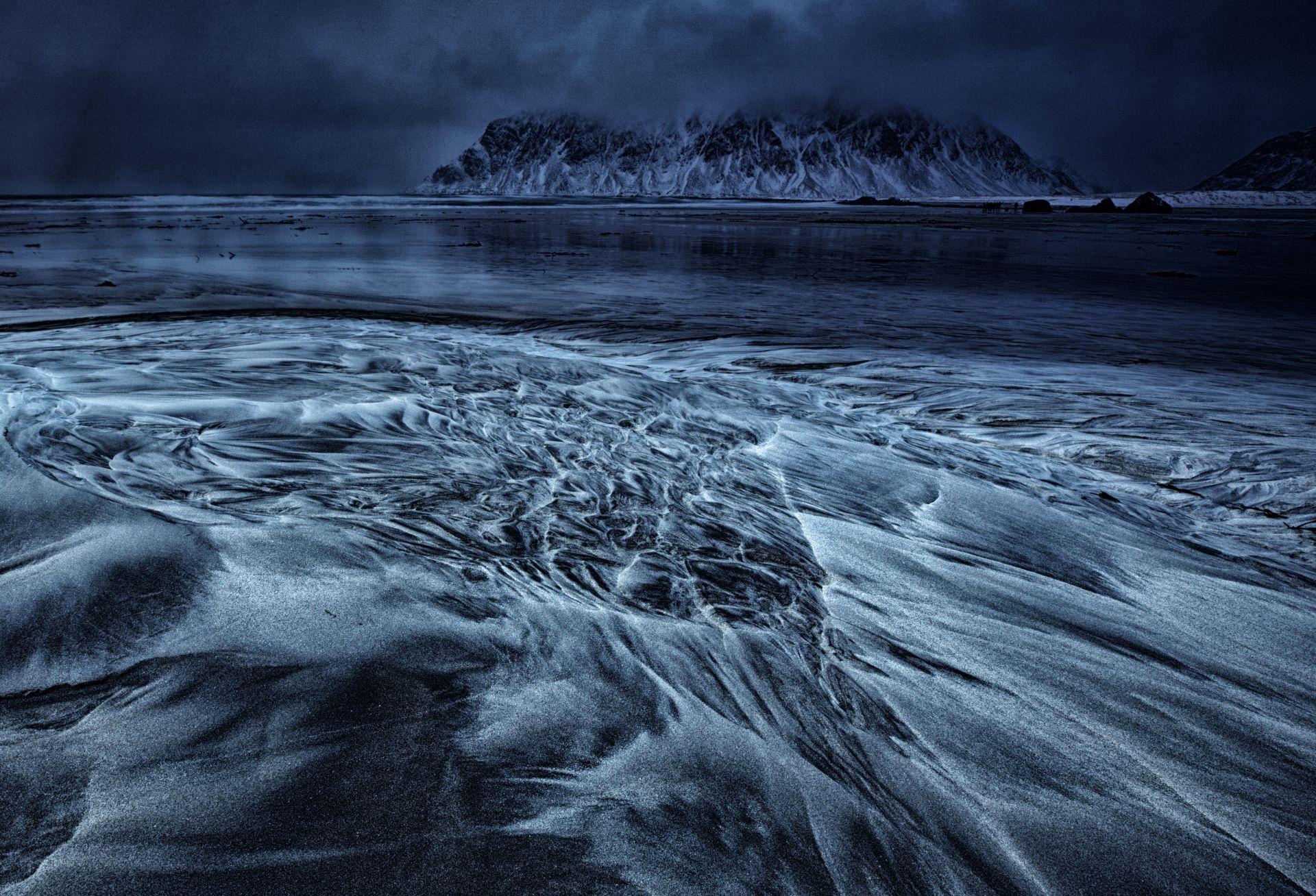 Fotó: Szabó Irma: Egy felhős nap<br />Az idén télen én is eljutottam Lofotenre, a saját szervezésemben. Tudom, sok fotós jár ide, de úgy gondolom ez a pillanat megismételhetetlen. A táj csodás, a sok apró sziget, a változó időjárás, a sarki fény, lenyűgözött. Mindegy, hogy milyen idő volt, esett, hóvihar volt, vagy jó hideg – mi reggeltől estig kint voltunk. Aznap igen felhős, borús idő volt, nem sok jóval kecsegtetett a természet. Nagyon tetszett, ahogy a szemközti hegyen megült a felhő. A hegy mintázata szinte olyan volt, mint előttem a homok, amit a dagály formázott. Gondoltam, milyen jól lehetne ezt a két formát kombinálni! Különböző beállításokkal és kompozícióval próbálkoztam. A komor hangulatot szerettem volna visszaadni. Remélem sikerült!<br /><br />Tájak<br />Dicséretre méltó