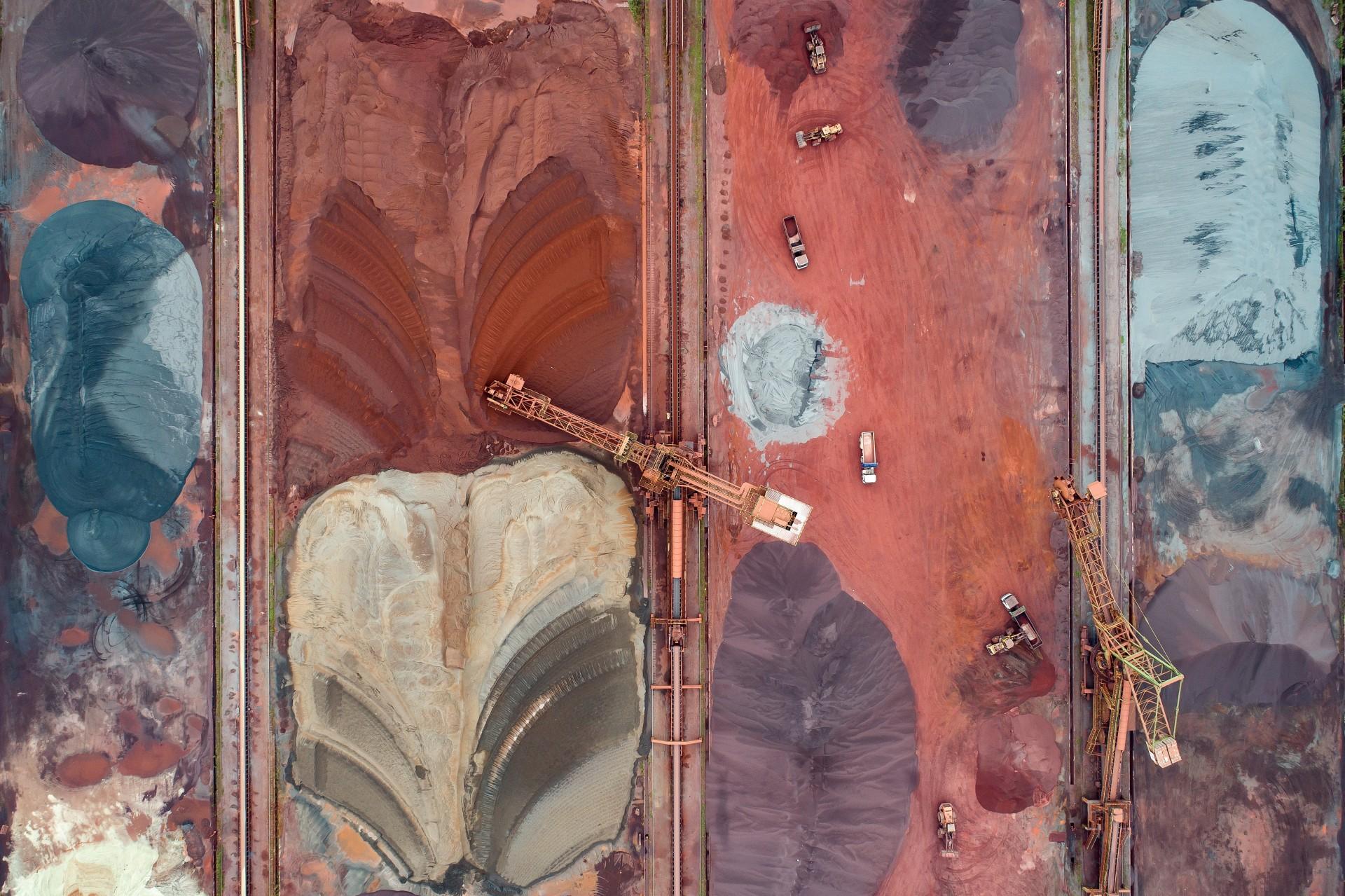 Fotó: Radisics Milán: Érc-piac<br />Kategória: Kezünkben a Föld<br />Helyezés: 2. díj<br /><br />Acélgyártás alapanyagainak tározó és osztályozó egységében darukkal töltik a teherautókat, amelyek a feldolgozandó nyersanyagot szállítják az érc-előkészítőkbe. A felülnézeti perspektíva a helynek egy afrikai füszerpiac hangulatát kölcsönzi. Gijon, Észak-Spanyolország.