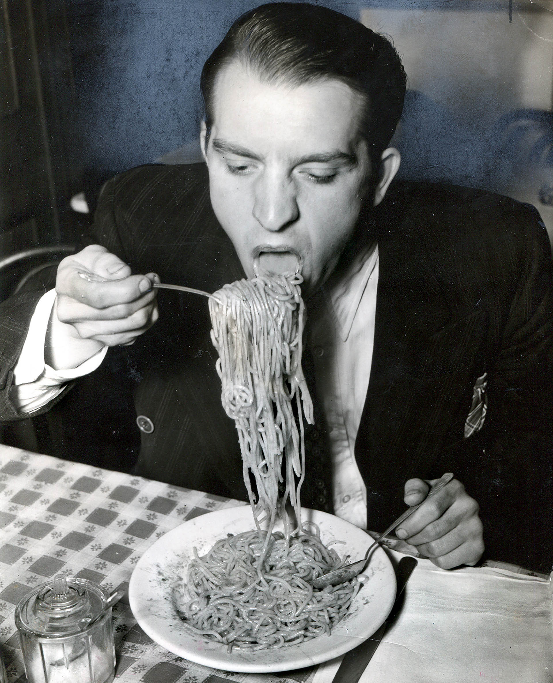 Fotó: Weegee: Phillip J. Stazzone is on WPA and enjoys his favourite food as he's heard that the Army doesn't go in very strong for serving spaghetti, 1940 © Weegee/International Center of Photography,