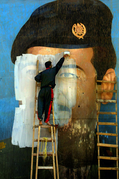 Fotó: Carolyn Cole: An image of Saddam Hussein, riddled with bullet holes, is painted over by Salem Yuel. Symbols of the leader disappeared quickly throughout Baghdad soon after US troops arrived in the city and took control, Baghdad, Iraq, April 2003<br />© Carolyn Cole / Los Angeles Times