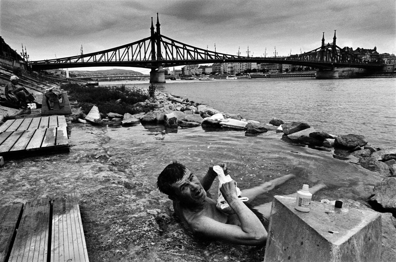 Fotó: Molnár Zoltán: Fürdőző hajléktalan a budai alsó rakparton, Budapesten.