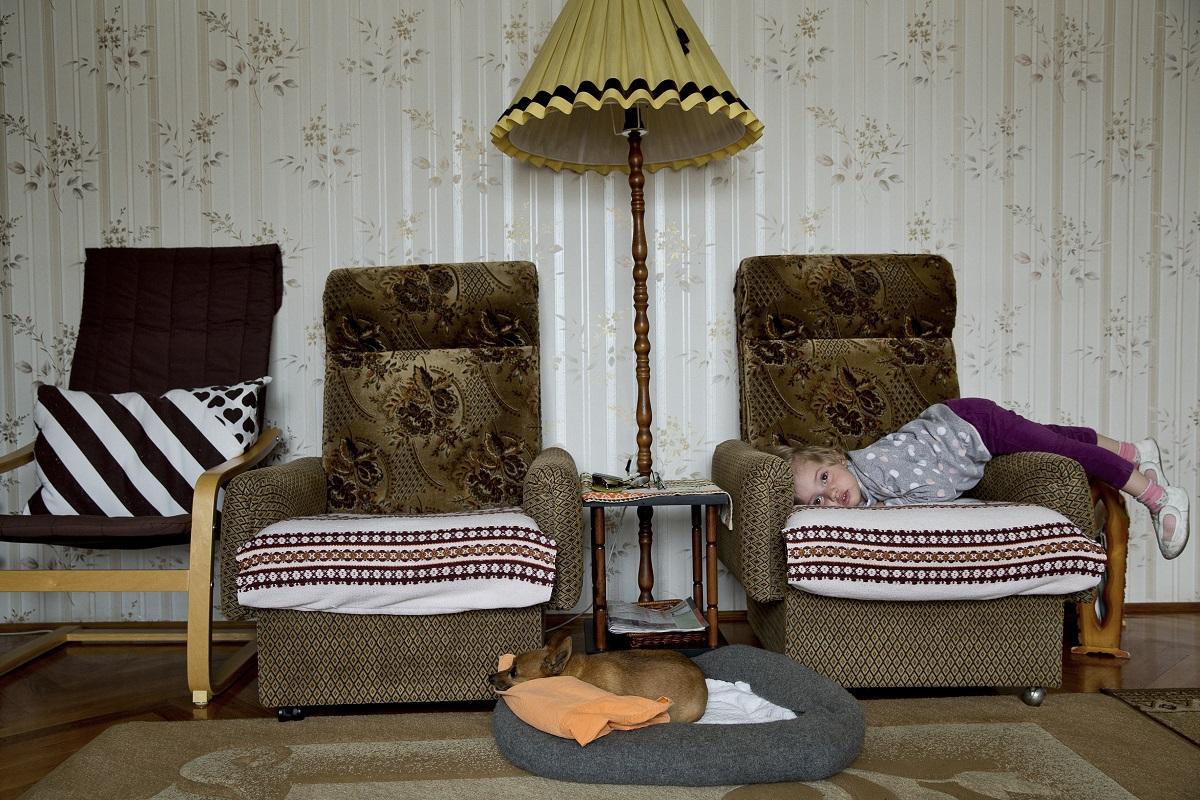 Mindennapi élet (sorozat) 1. díj<br /><br />Fotó: Ajpek Orsolya: Otthon, édes otthon. Részlet a sorozatból.<br /><br />Közös fedél alatt, különböző közösségekben éljük életünket világszerte. Ennek alapegysége a család és az ennek otthont adó családi ház. Amíg évtizedekkel ezelőtt a nagycsalád, azaz több generáció együttélése még nem számított rendkívülinek, ma ez lényegesen ritkábban fordul elő. 172 négyzetméter, 13 fő, 4 generáció. Ez az én szűk családom, ha szigorúan számokban mérem magunkat. A színhely a magyar főváros külkerületében álló régi kis ház a dédszülőkkel, hozzáépítve az újabb és nagyobb házrész a szüleimmel, a húgommal és az ő családjával. A hétvégén és az ünnepeken érkező nővéremmel és az ő családjával pedig maximumon van a létszám és néha a tűrőképesség is. Az együttélés önkéntes, de kényszerűségből is fakad. A négygenerációs családban szeretet, tapasztalat, igény vegyül össze; az egészen idilli pillanatoktól a teljesen abszurdig mindent produkál és mindent ki is bír.