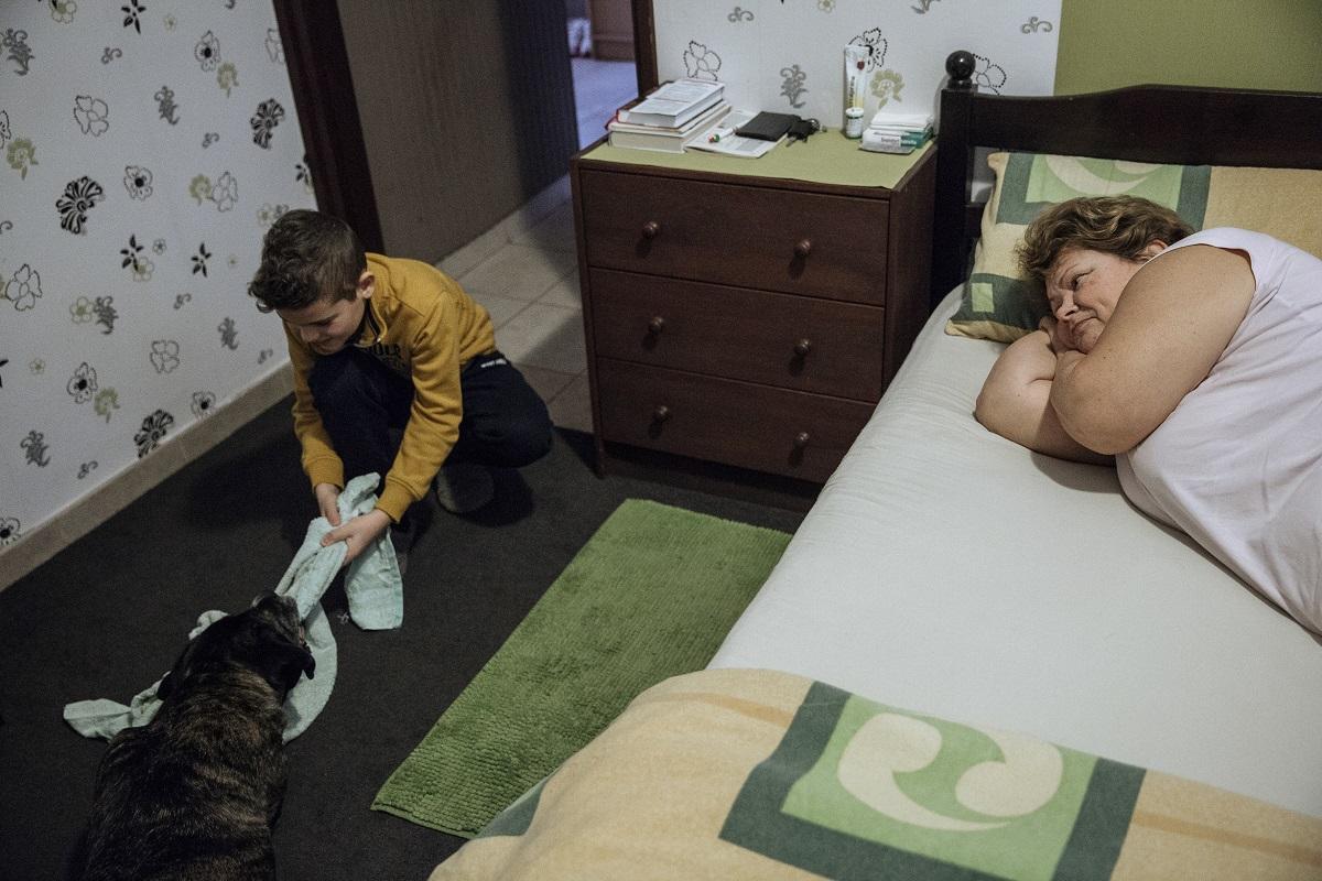 Mindennapi élet (sorozat) 1. díj<br /><br />Fotó: Ajpek Orsolya: Otthon, édes otthon. Részlet a sorozatból.<br /><br />172 négyzetméter, 13 fő, 4 generáció. Ez az én szűk családom, ha szigorúan számokban mérem magunkat. A színhely a magyar főváros külkerületében álló régi kis ház a dédszülőkkel, hozzáépítve az újabb és nagyobb házrész a szüleimmel, a húgommal és az ő családjával. A hétvégén és az ünnepeken érkező nővéremmel és az ő családjával pedig maximumon van a létszám és néha a tűrőképesség is. Az együttélés önkéntes, de kényszerűségből is fakad. A négygenerációs családban szeretet, tapasztalat, igény vegyül össze; az egészen idilli pillanatoktól a teljesen abszurdig mindent produkál és mindent ki is bír.