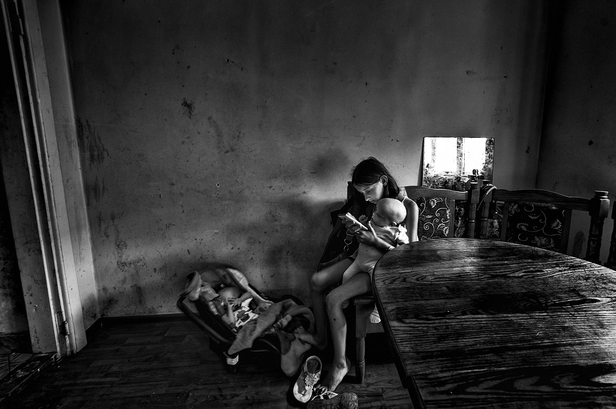Társadalomábrázolás 1. díj<br /><br />Fotó: Balassa László: Csend<br /><br />Egy kilenc gyermekes kárpátaljai család legnagyobb gyermeke két kistestvérével. Gyakorlatilag ő neveli a testvéreit. Édesapja szibériában dolgozik édesanyja munkanélküli, aki a kilenc gyerek mellett nem is tudna dolgozni.<br />