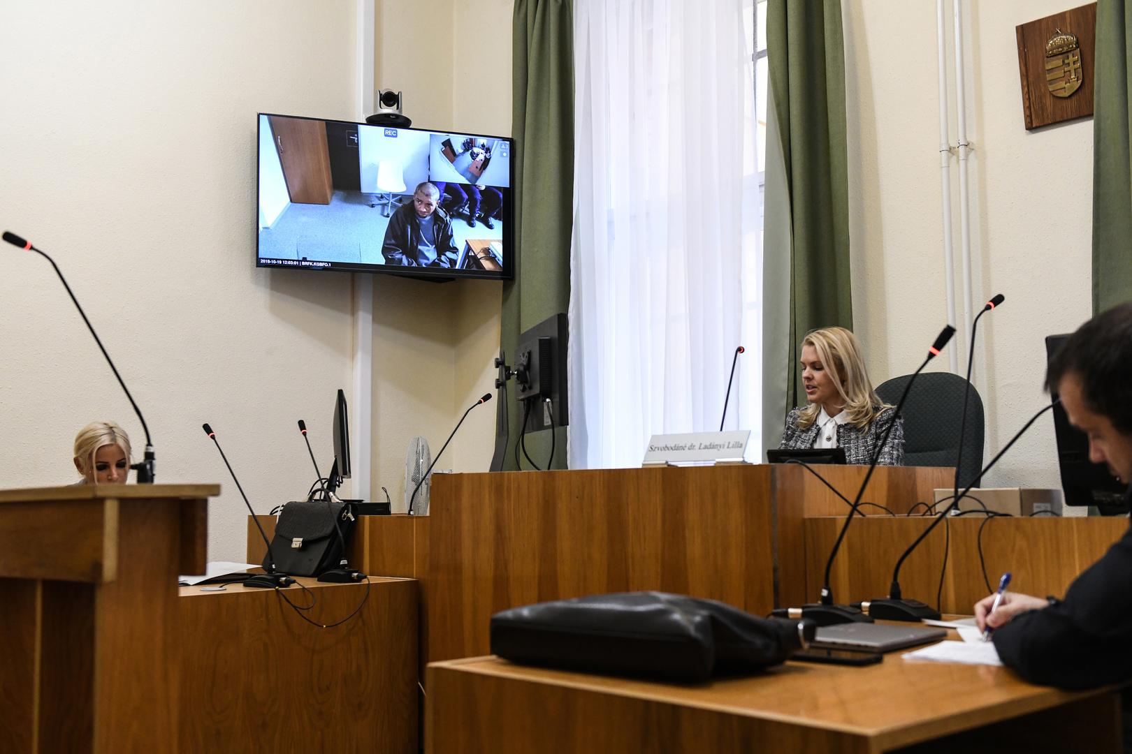 """Társadalomábrázolás, dokumentarista fotográfia (egyedi)<br />2. díj: Reviczky Zsolt (HVG): No go zóna<br /><br />Fotó: 2018 október 15-én egy új törvény lépett életbe, amely sokkal súlyosabban bünteti a hajléktalanokat mint a korábbi rendelkezés. Manapság a hajléktalan embereket akár börtönbe is zárhatják ha nincs hol lakniuk. Az egyik legelső ilyen tárgyaláson a vádlottat be sem engedték a tárgyalóterembe. Ugyanazon épületben, de egy másik szobában tartózkodott, és zártláncú videórendszer segítségével """"vett részt"""" a tárgyaláson. A bírónak vagy az ügyésznek még csak közvetlenül a szemébe sem kellett néznie a hajléktalan embernek."""