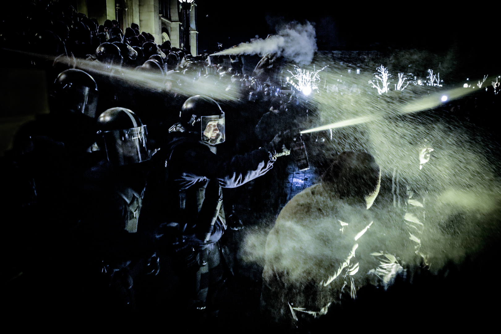 Hír-, eseményfotó<br />3. díj: Huszti István (Index.hu): Oszlatás<br /><br />Fotó: Könnygázzal oszlatják a feldühödött tömeget 2018 december 12-én a Parlament lépcsőjénél a rendőrök. Spontán tüntetések kezdődtek Budapesten miután a Parlament elfogadta a túlóratörvényt.