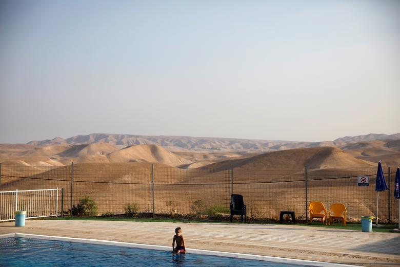 Fotó: Ronen Zvulun: Egy fiú ül a medence mellett a Vered Yericho izraeli településen, a megszállt Ciszjordániában, 2019. szeptember 11. © Reuters/Ronen Zvulun