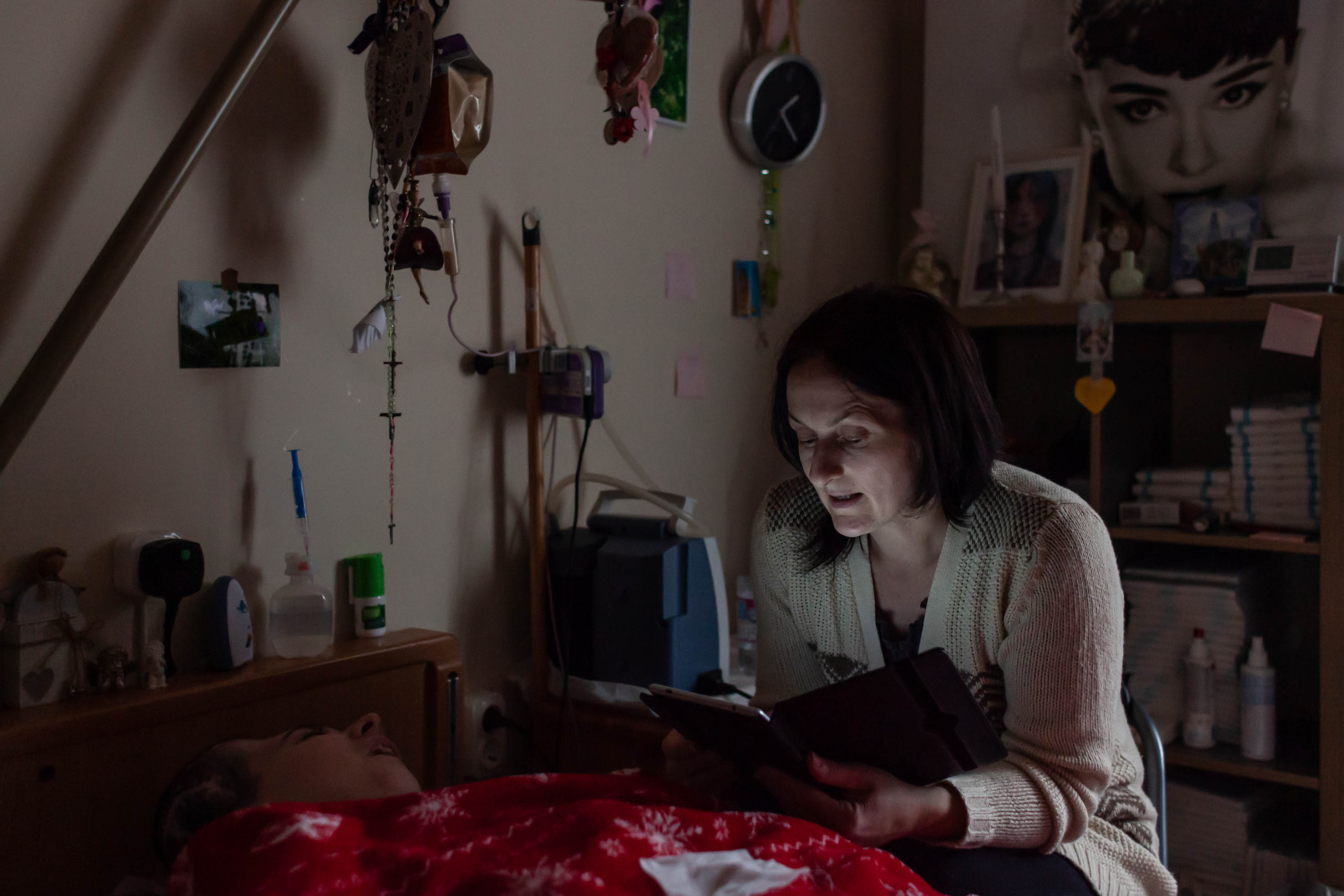 Márti rendszeresen felolvas lánya kedvenc könyvéből. Az élőbeszéd, az énekhang mással nem pótolható személyességet ad az éber kómás betegeknek.<br /><br />Fotó: Kovács Bea / Magyar Sajtófotó Pályázat