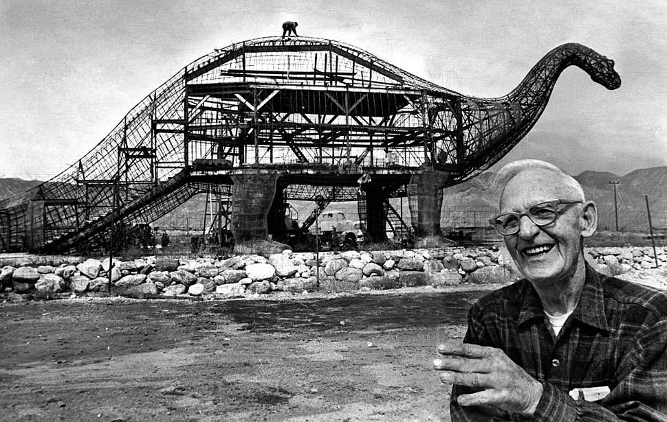 Fotó: Claude K. Bell szobrászművész brontoszauruszával, Cabazon mellett. A Knott's Berry Farm szobrásza és portréművésze 1958-ban nyitotta meg a Wheel Inn kávézót és a látogatók elkápráztatásáért elkezdett dinoszauruszokat építeni. 1970. március 23. © UCLA Library/Los Angeles Times