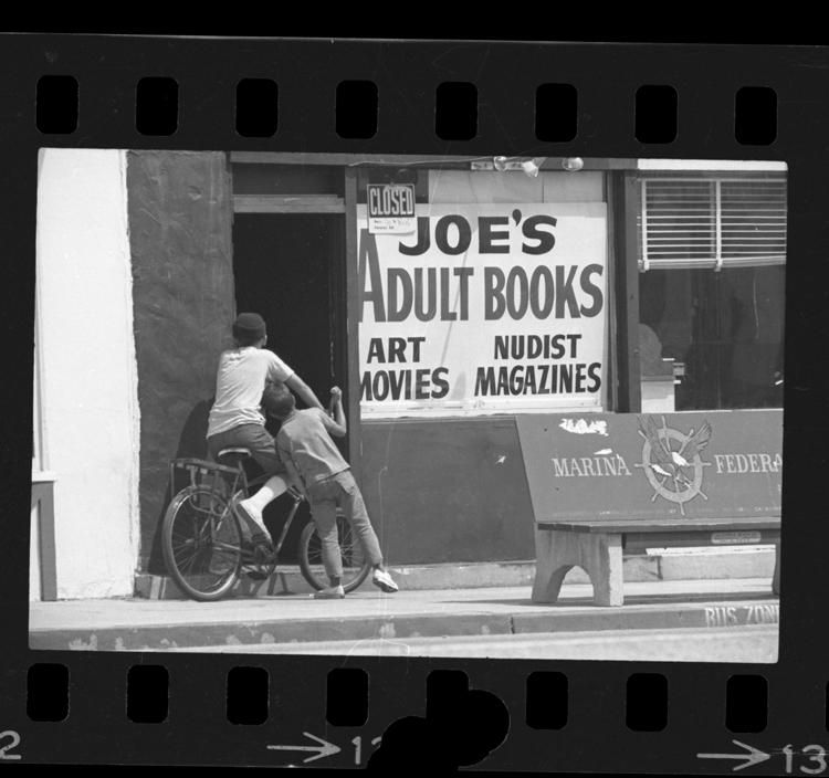 Fotó: Két kiskorú leskelődik egy felnőtteknek szóló könyveket forgalmazó bolt ajatján, Lennox, Calif., 1969 © UCLA Library/Los Angeles Times