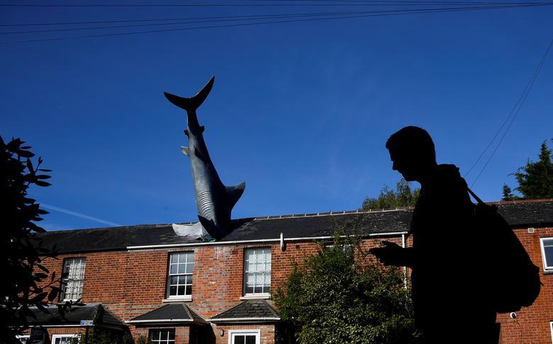 Fotó: Toby Melville: Egy férfi sétál az 'Untitled 1986' nevű installáció mellett, amelyet általában 'The Headington Shark'-nak hívnak, és amelyet 1986-ban a nagaszaki támadás 41. évfordulójára készítettek. A cápa formájú szobor egy ház tetőjébe ágyazódik, Nagy-Britannia, Oxford, 2019. május 14. © Reuters/Toby Melville