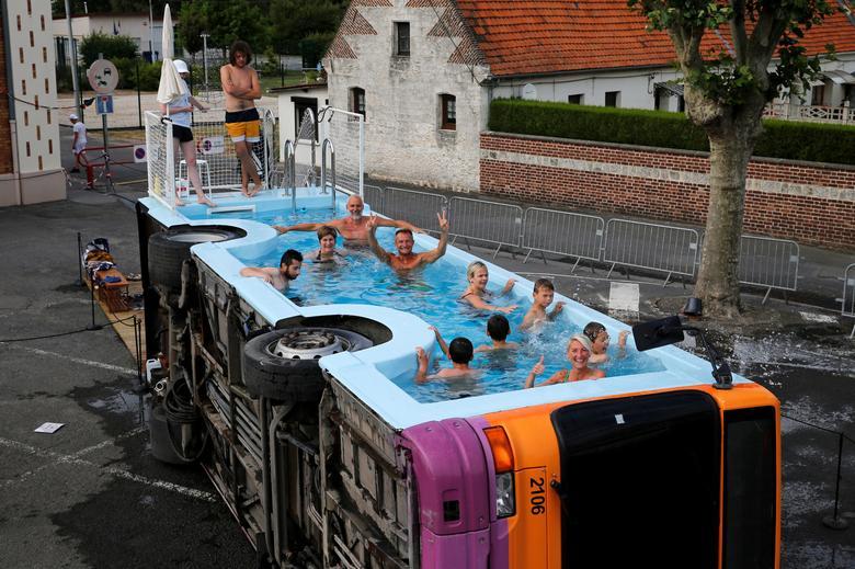 """Fotó: Pascal Rossignol: Az emberek a """"le bus piscine"""" elnevezésű, leselejtezett városi autóbuszban fürödnek, amely a francia művész, Benedetto Bufalino alkotása, Gosnay, Franciaország, Bethune közelében, 2019. július 10. © Reuters/Pascal Rossignol"""