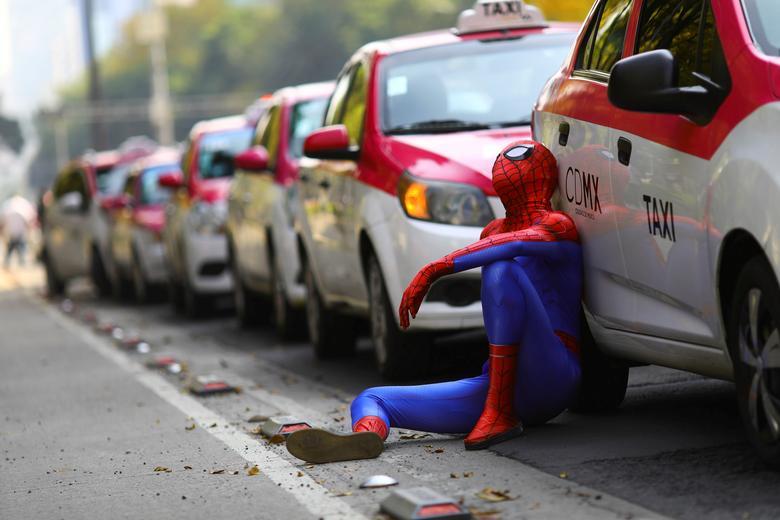 Fotó: Egy pókembernek öltözött személy ül a taxik mellett, miközben a taxisofőrök az olyan applikációk ellen tiltakoznak, mint az Uber, a Cabify és a Didi, Angel de la Independencia emlékmű, Mexikóváros, Mexikóban, 2020. október 12. © REUTERS / Edgard Garrido
