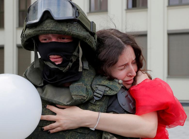 Fotó: Egy résztvevő átkarolja a belorusz belügyminisztérium csapatának egyik tagját, aki egy ellenzéki tüntetés során őrködik, hogy tiltakozzon a rendőri erőszak ellen, és elutasítsa az elnökválasztási eredményeket, Függetlenség tér, Minszk, 2020. augusztus 14. REUTERS / Vaszilij Fedosenko