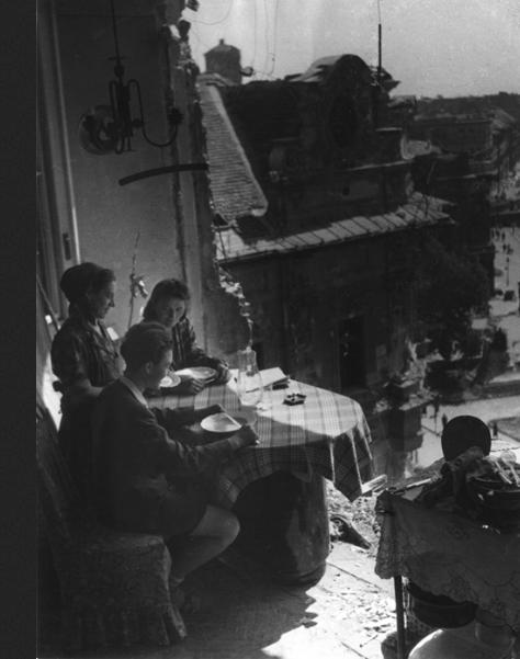 Fotó: Escher Károly: Ebéd a romos erkélyen, Budapest, 1945 <br />HUNGART © 2020<br />A fotót a Magyar Fotográfiai Múzeum gyűjteményében őrzik.<br />