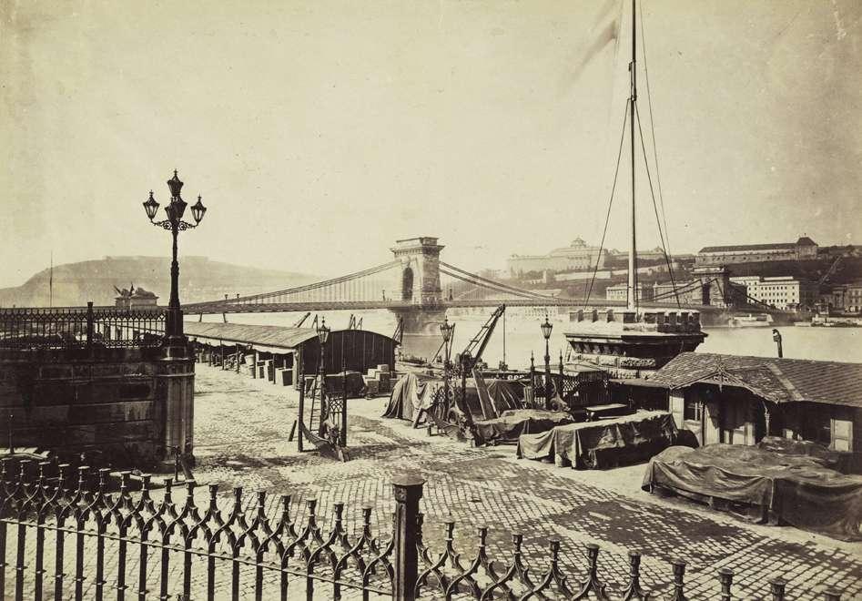 Fotó: Klösz György: teherhajó kikötő és raktárai a Széchenyi (Rudolf) rakparton. Háttérben a Széchenyi Lánchíd és a Királyi Palota (ma Budavári Palota). A felvétel 1880-1890 között készült. A kép forrását kérjük így adja meg: Fortepan / Budapest Főváros Levéltára. Levéltári jelzet: HU.BFL.XV.19.d.1.05.050