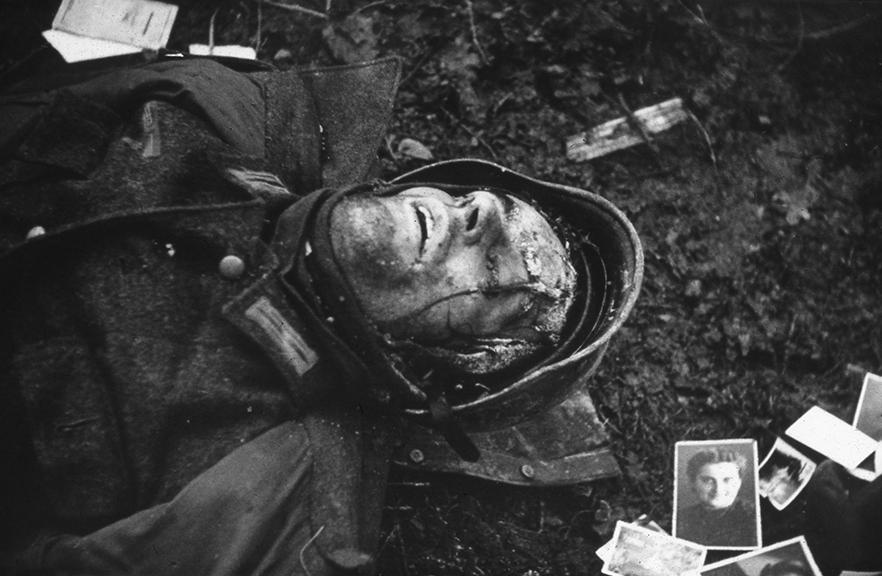07_egy_halott_nemet_katona_fekszik_a_csaladtagjairol_keszult_fenykepek_kozott_hurtgen-erdo_nemetorszag_1945_januar.jpg