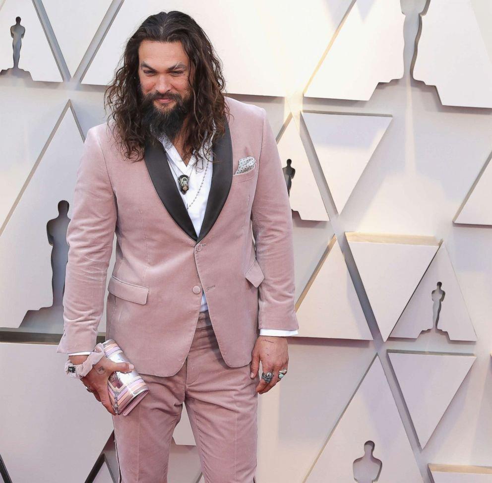 Vegyél példát Jason Momoáról, aki pink öltönyben is mesterien pózol, a felesége táskájával