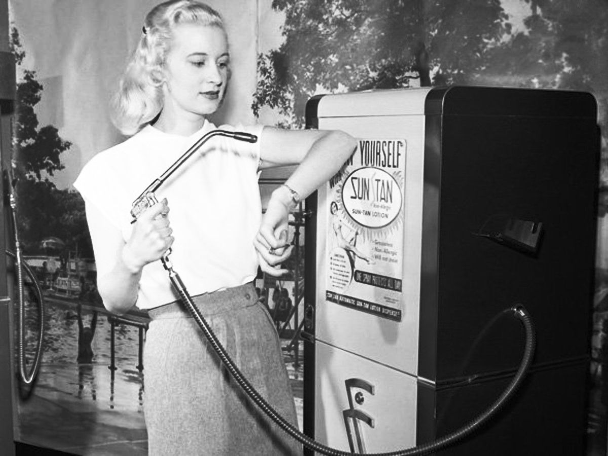 Betty Dutter modell 1949-ben, amint bemutatja a strandokon, uszodákban és teniszpályákon kihelyezett napvédőszert árusító automatát.