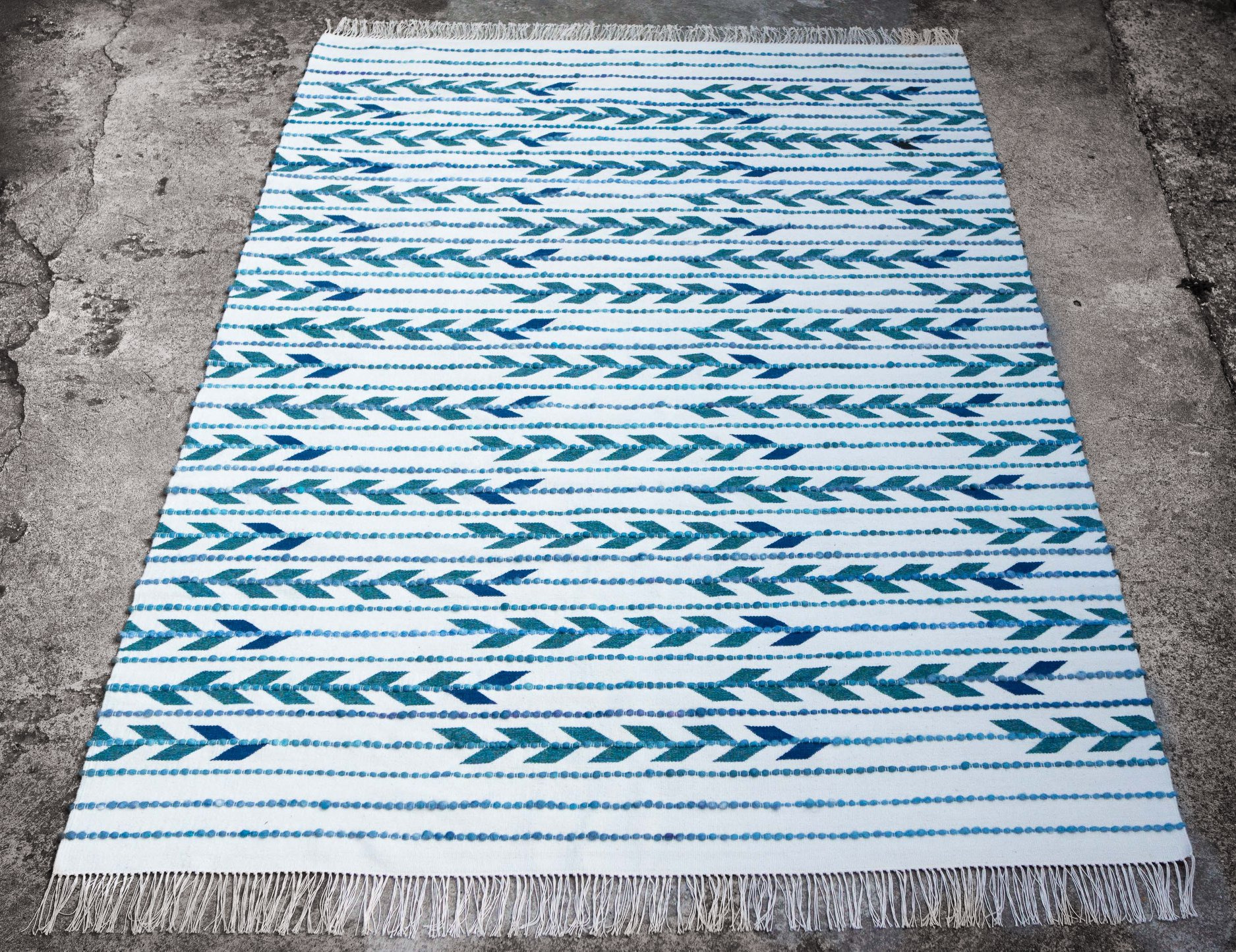 Timim hagyományos technikával, szövőszéken szövött színes gyapjúszőnyegeket készít magfonalas díszítősorral, egymással harmonizáló kék, zöld és lila színek játékával. Csodás!<br />timim.meska.hu