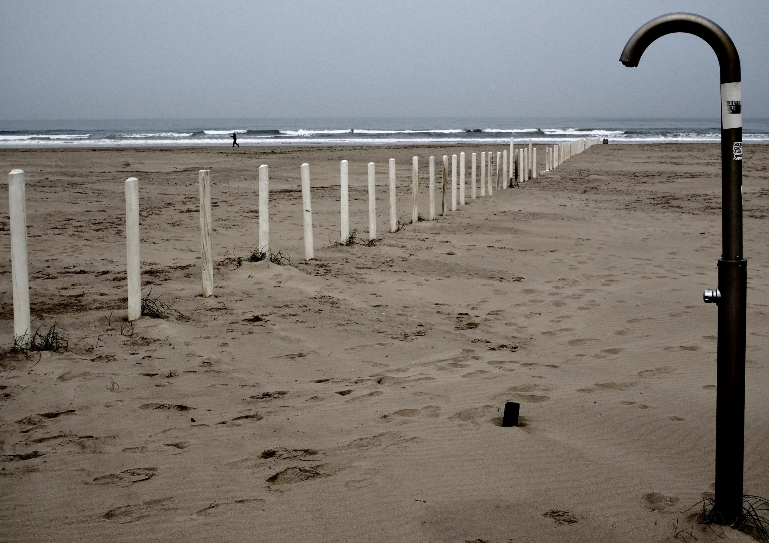 Castlerock – A kihalt és majdnem teljesen üres parton lábnyomok láthatóak. A zuhanyzóval le lehet mosni a homokot, amit egy titokzatos határ oszt ketté. (Richard Morgan / The Independent)