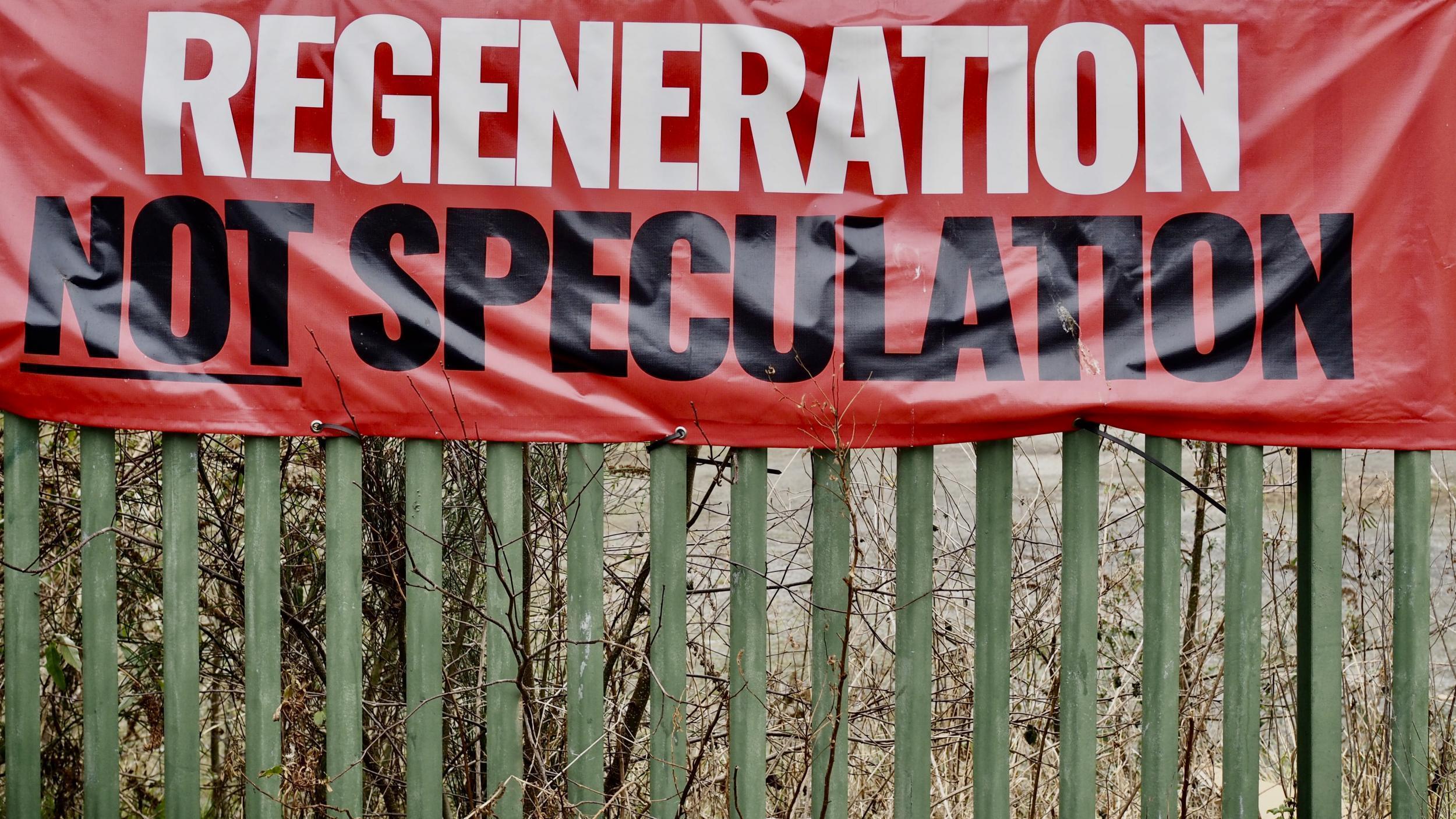 """Belfast: """"Renovációt, nem spekulációt"""" – Egy gazdátlan földterület kapuja, ahol semmi nem épül, semmit nem terveznek, és ahol egy molinó követeli, hogy alkossanak valami újat. (Richard Morgan / The Independent)"""