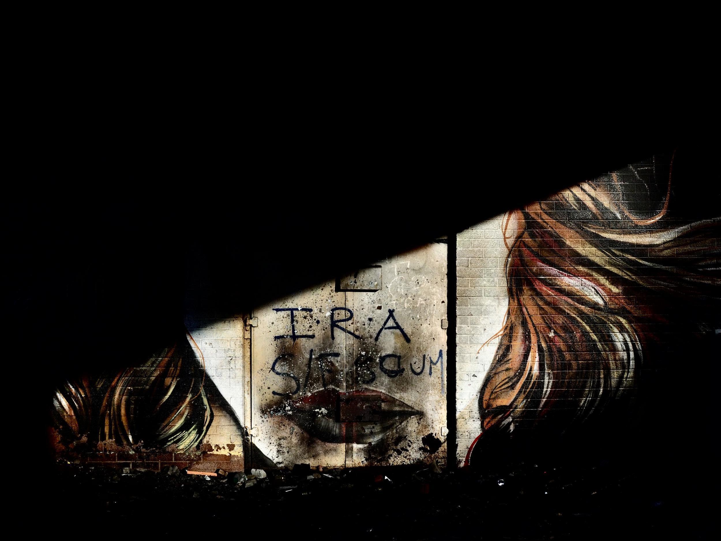 """Derry, Londonderry: """"IRA – geci SIF"""" – Egy autóhíd alatt egy vörös hajú és vörösre rúzsozott nő arca, akire egy IRA-t támogató, valamint a Közösségi Beruházási Alapot sértegető üzenetet tetováltak. (Richard Morgan / The Independent)"""
