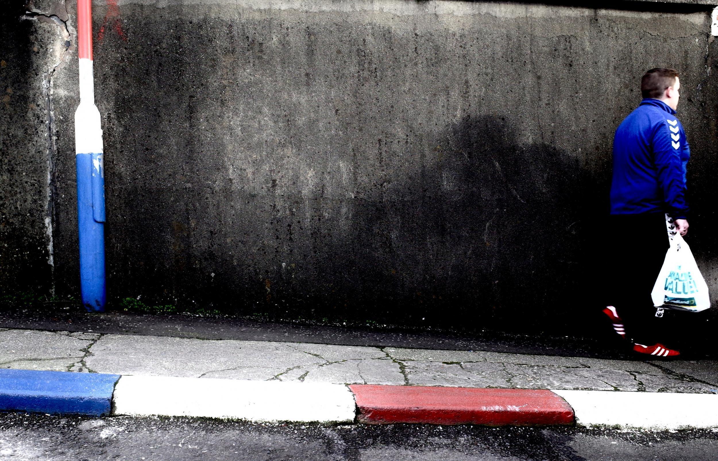 Derry, Londonderry: A Fountain negyed falfestményei, ahol a szegélyek és a lámpaoszlopokat a brit lobogó piros-fehér-kékjére színezték. Egy arra sétáló fiú az ugyanilyen színű ruhájával beleolvad a környezetbe. (Richard Morgan / The Independent)