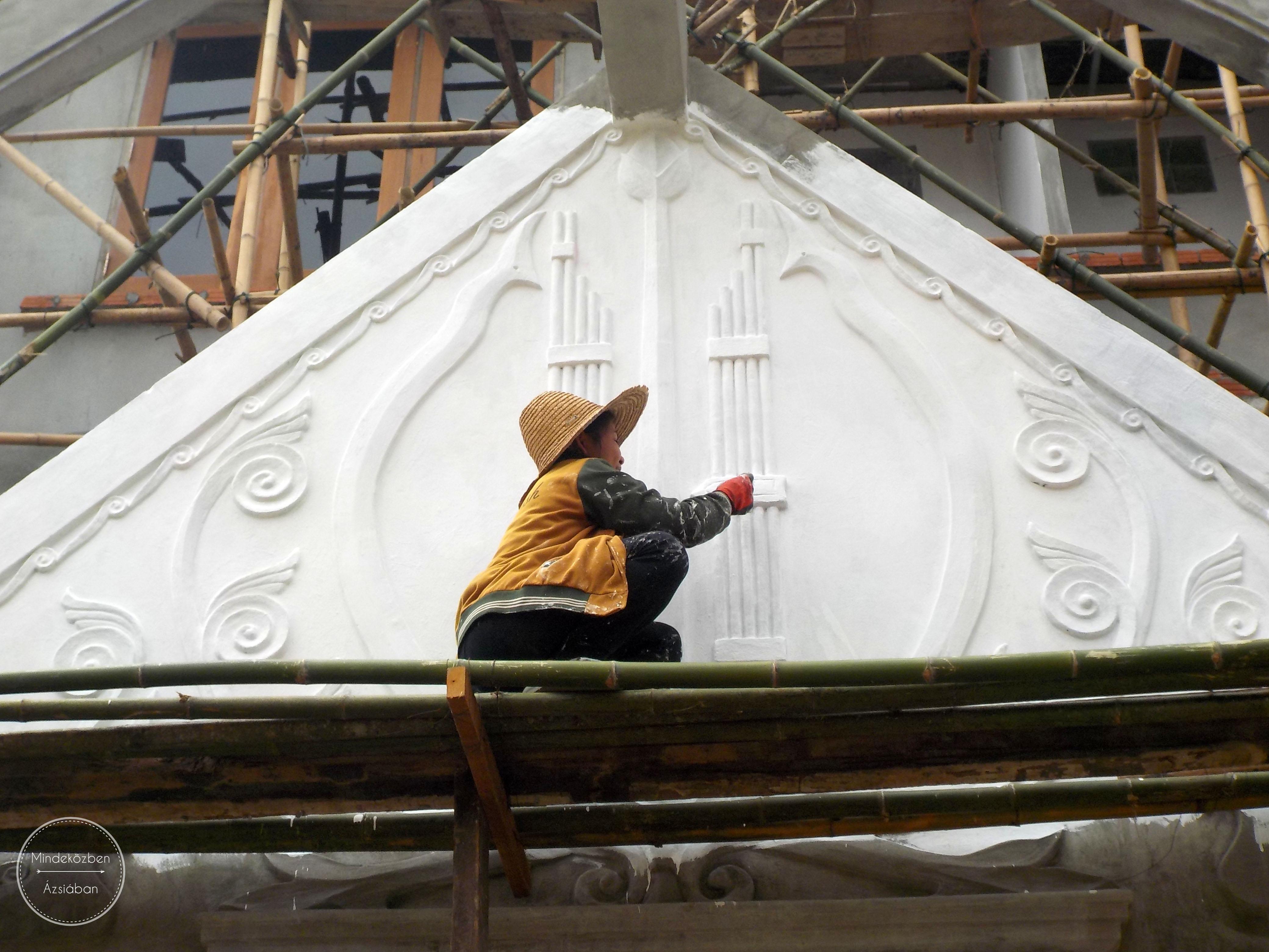 Bambuszból készített állványon helyi nő restaurál egy házat.